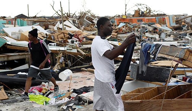A man hangs his clothing amid the rubble of destroyed homes Sept. 6, 2019, after Hurricane Dorian hit the Abaco Islands in Marsh Harbour, Bahamas. In the wake of Hurricane Dorian's brutal blasting of the Bahamas, Catholic organizations in Florida continued to raise funds to aid victims there. (CNS photo/Marco Bello, Reuters) See DORIAN-FLORIDA-AID Sept. 6, 2019.